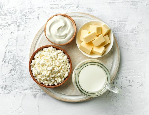 Diverse melkproducten op witte houten snijplank, bovenaanzicht