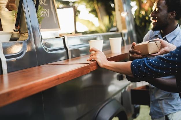 Diverse mensen die gastronomisch eten bestellen bij de balie van de foodtruck buiten - focus op de hand van de vrouw