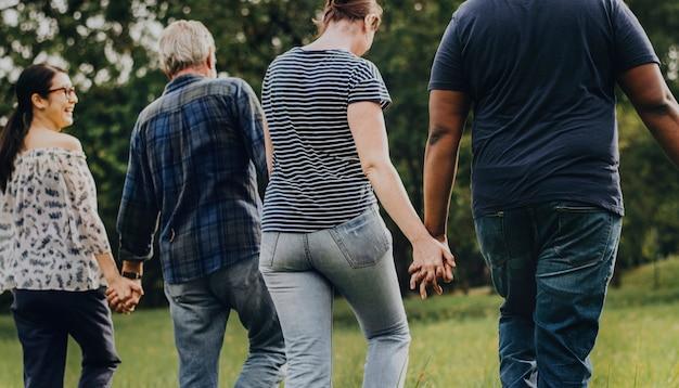 Diverse mensen die handen houden en in het park lopen