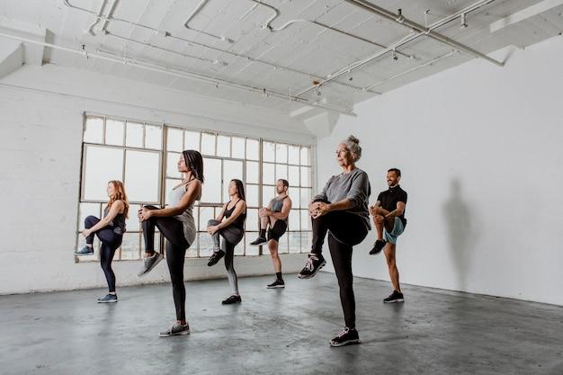 Diverse mensen die hun knieën strekken in een yogales