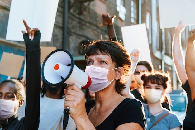Diverse mensen met masker protesteren tijdens covid-19 pandemie