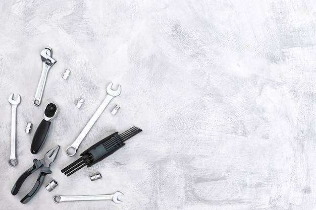 Diverse metalen gereedschap tangen moersleutels schroevendraaiers bits bovenaanzicht op een betonnen grijze vloer