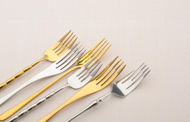 Diverse metalen vorken op een lichte tafel. goud en zilver bestek, kopie ruimte
