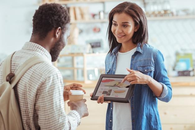 Diverse mogelijkheden. mooie jonge vrouw die een tablet met het menu van koffie houdt en de verscheidenheid aan snacks aan haar vriend toont, stelt voor om iets te kiezen