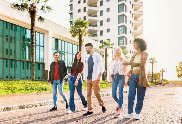 Diverse multiculturele groep jonge vrienden die in een rij door een stedelijke straat lopen, kletsend en lachend verlicht door de zon in een lage hoek