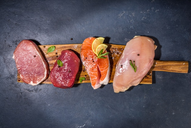 Diverse natuurlijke voeding, hoge dierlijke eiwitbronnen - varkensvlees, rundvlees steaks, kipfilet, eieren, zalm vis op witte tafel achtergrond bovenaanzicht kopie ruimte