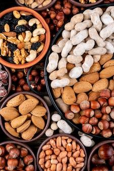 Diverse noten en gedroogde vruchten in verschillende kommen en borden met pecannoten, pistachenoten, amandel, pinda, cashew, pijnboompitten bovenaanzicht