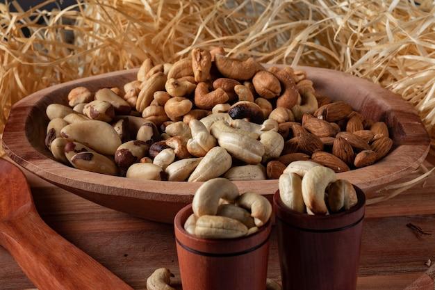 Diverse noten in een houten kom en in twee houten kopjes met stro achtergrond. hoofdnoten van de braziliaanse keuken.