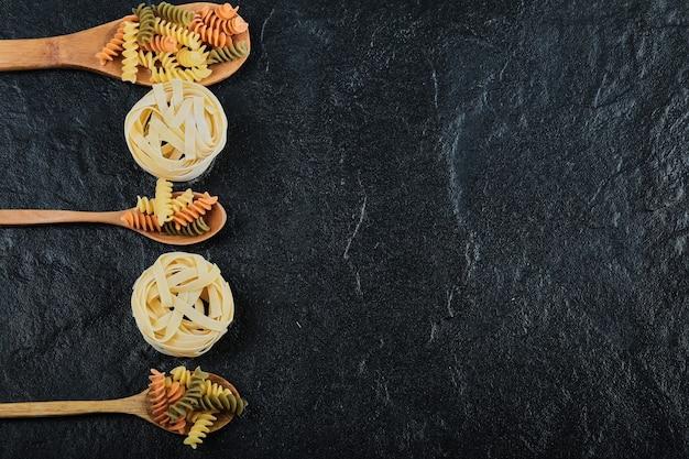 Diverse ongekookte deegwaren op houten lepels over donker.