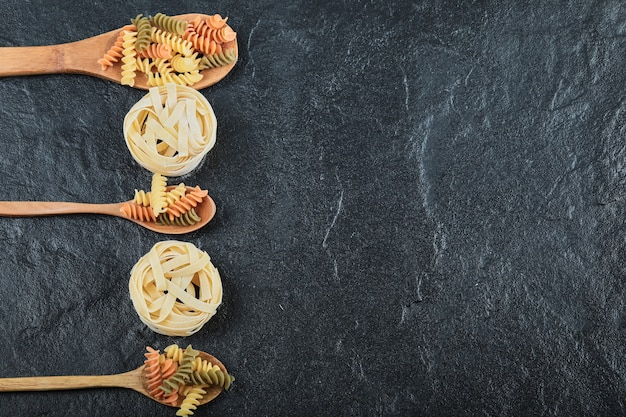 Diverse ongekookte pasta op houten lepels over donkere achtergrond.