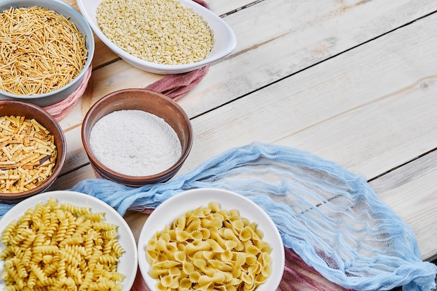 Diverse ongekookte pastakommen op houten tafel met blauw tafelkleed.