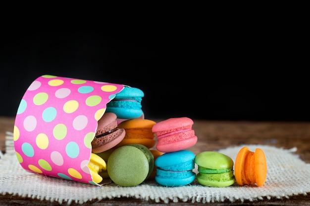Diverse op smaak gebrachte macarons of makaron in document kop op donkere achtergrond.