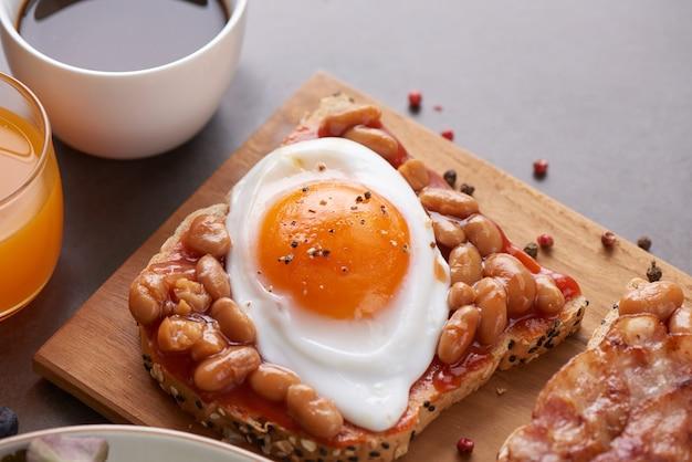 Diverse open sandwiches gemaakt van bruin volkorenbrood met tomatensaus, witte bonen, spek, gebakken ei.