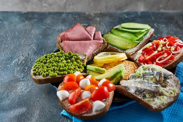 Diverse open sandwiches, sandwiches met plakjes zuurdesem met verschillende vullingen op een bord