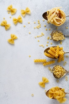 Diverse pasta in ijzeren lepels op grijze betonnen tafel. anellini-pasta. koken concept. bovenaanzicht.