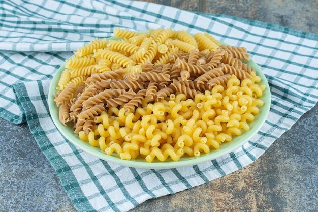 Diverse pasta's in kom op de handdoek, op de marmeren achtergrond.