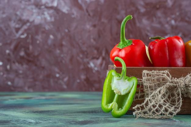 Diverse peper in een houten kist op het marmeren oppervlak