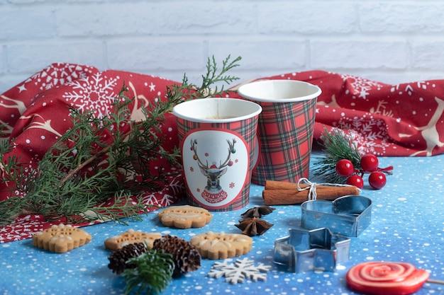 Diverse peperkoekkoekjes, kopjes aromakoffie en ornamenten op blauwe winterachtergrond. hoge kwaliteit foto