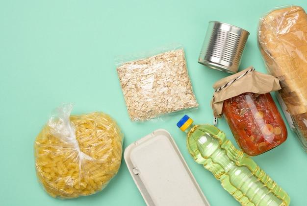Diverse producten, brood, pasta, zonnebloemolie in een plastic fles en conservering, bovenaanzicht