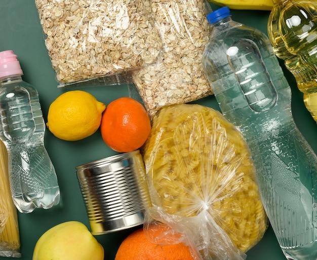Diverse producten, fruit, pasta, zonnebloemolie in een plastic fles en conservering, bovenaanzicht. donatie concept