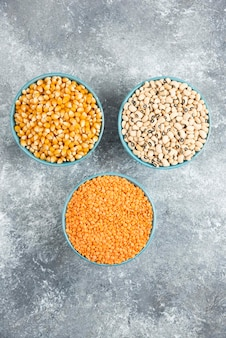 Diverse rauwe bonen, maïskorrels en rode linzen op marmeren tafel.