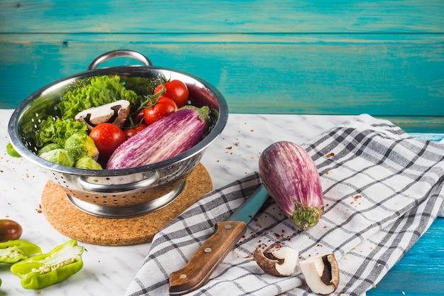 Diverse rauwe groenten in vergiet over marmeren bureau