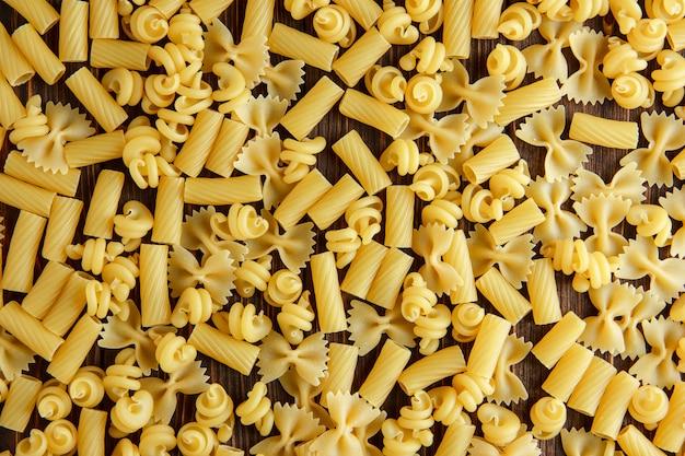 Diverse rauwe pasta op een houten tafel. plat lag.