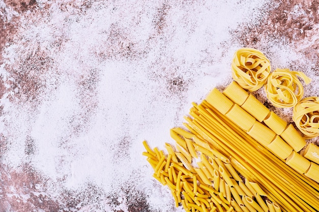 Diverse rauwe pasta's op houten tafel.