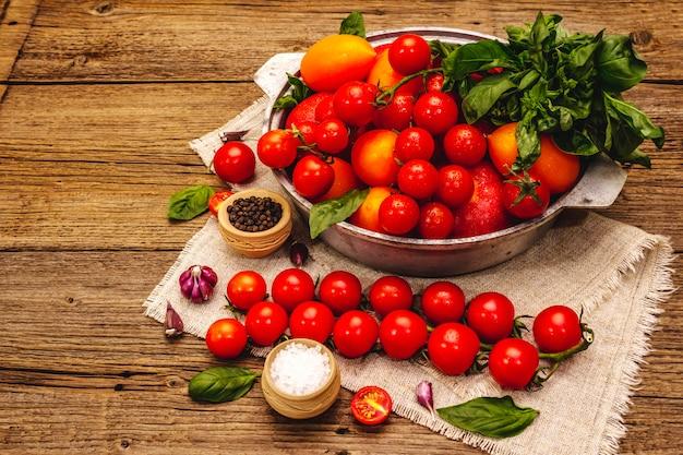 Diverse rijpe veelkleurige tomaten. jonge knoflook, verse basilicumblaadjes, zout, kruiden