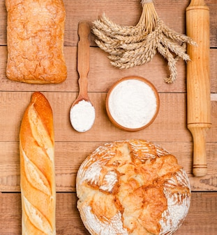 Diverse rustieke knapperige broden en broodjes op houten planken.