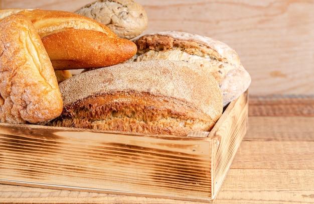 Diverse rustieke knapperige broodjes en brood in een doos op een houten achtergrond.