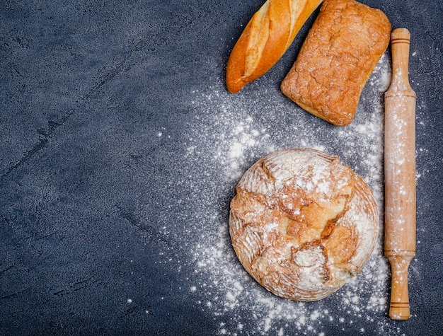 Diverse rustieke krokante broodjes met brood, tarwebloem, deegroller