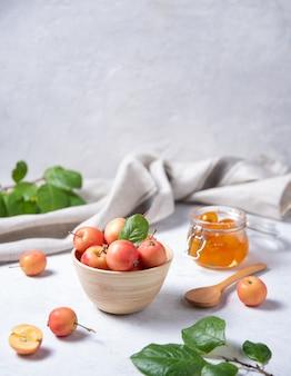 Diverse sappige mini appels in een houten kom en een potje jam op een lichte achtergrond. vooraanzicht en kopieerruimte
