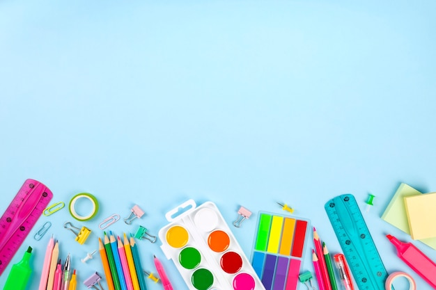 Diverse school kantoor en schilderen leveringen op blauwe muur. terug naar school-concept. bovenaanzicht. kopieer ruimte