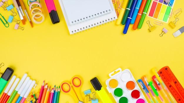 Diverse schoolkantoor en schilderbenodigdheden op gele achtergrond. terug naar schoolconcept. bovenaanzicht. ruimte kopiëren