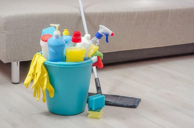 Diverse schoonmaakproducten met servetten, sponzen en handschoenen in een blauwe emmer op de kamer.