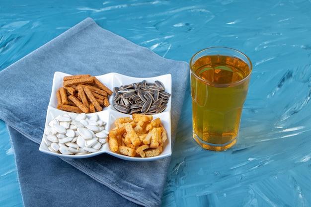 Diverse snackkommen naast glas bier op een handdoek, op het blauwe oppervlak.