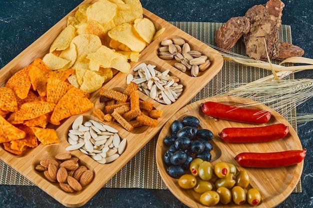 Diverse snacks, een bord worst, kaviaar en olijven op een houten tafel.