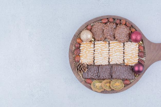 Diverse snacks en kerstballen op een houten bord.