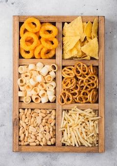 Diverse snacks in vintage houten doos op lichte keukentafel. uienringen, nacho's, zoute pinda's met aardappelstaafjes en pretzels. geschikt voor bier en frisdranken.
