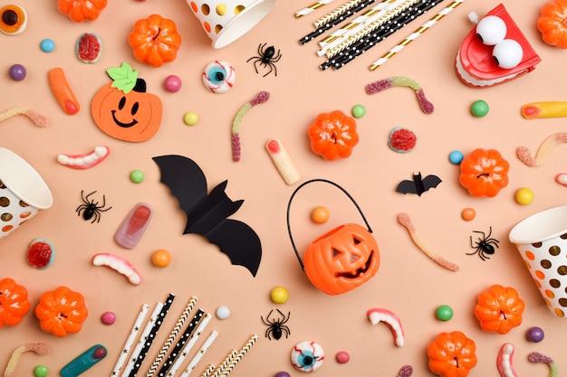 Diverse snoepjes op een oranje achtergrond met een plek voor tekst. achtergrond voor de halloween-vakantie. platte lay-out, bovenaanzicht