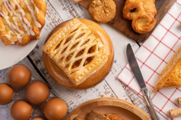 Diverse soorten brood en eieren op rode witte doek.