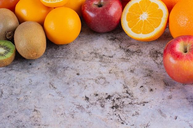 Diverse soorten citrusvruchten op grijs.