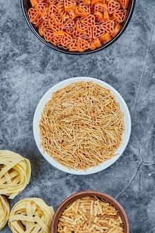 Diverse soorten droge pasta op de marmeren tafel.