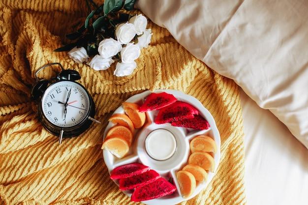 Diverse soorten fruit en melk voor het ontbijt met klok met 7 uur en roze bloem op het bed