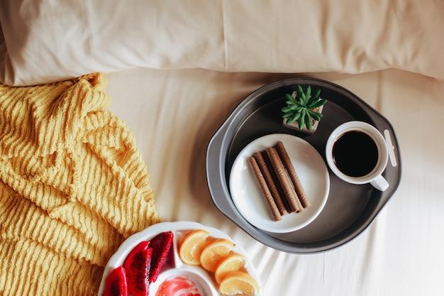 Diverse soorten fruit met tussendoortje en een kopje koffie voor het ontbijt op bed