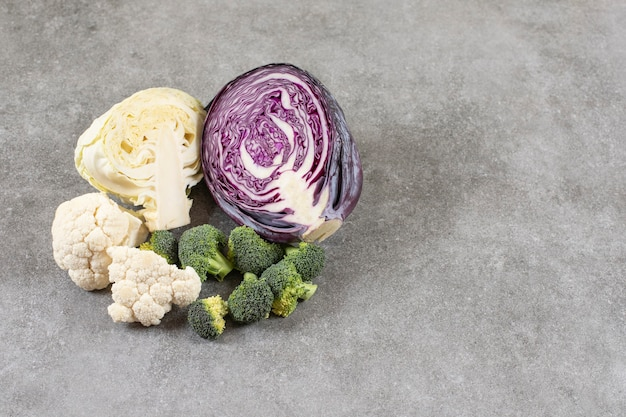 Diverse soorten gezonde groenten op een stenen achtergrond.