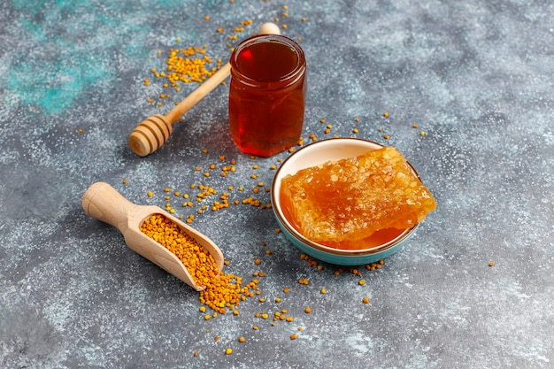 Diverse soorten honing in glazen potten, honingraat en pollen.
