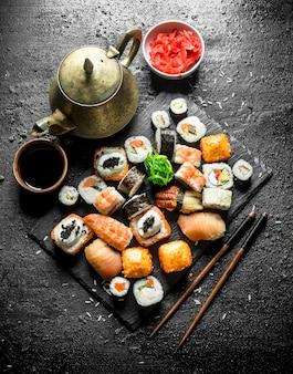 Diverse soorten japanse sushirolletjes met gember en sojasaus. op zwarte rustieke tafel