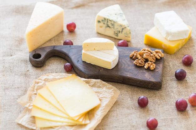 Diverse soorten kaas, blauwe kaas en brie met druiven en noten.